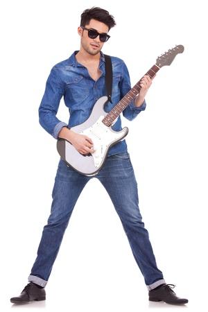 jonge casual man met een gitaar op een witte achtergrond Stockfoto