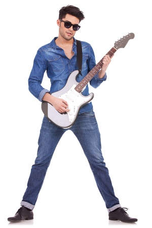 young casual man playing a guitar on a white background Stock Photo