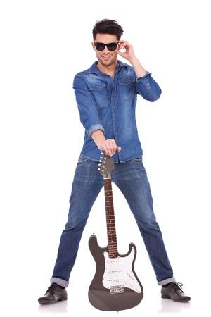 legs spread: Lunghezza quadro completo di un uomo casual giovane in possesso di una chitarra tra le sue gambe divaricate e tenendo gli occhiali da sole