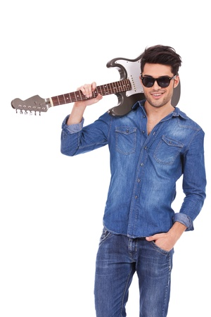 playing the guitar: smiling casual young man with sunglasses holding a hand in his pocket and a guitar on his shoulder  isolated on white background