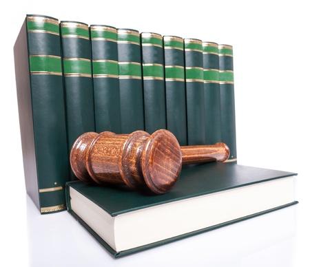 stapel wetboeken en een rechter hamer op een boek over witte backgroun