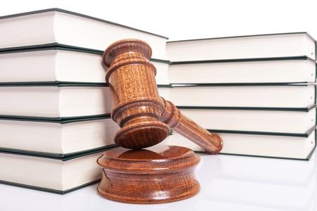 orden judicial: muchos libros de derecho y un mazo de madera jueces sobre fondo blanco Foto de archivo