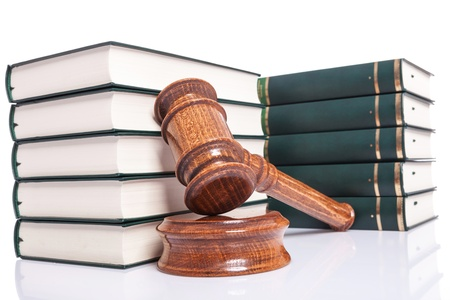 Judges wooden gavel leaning against law books on white background Stock Photo - 15736721