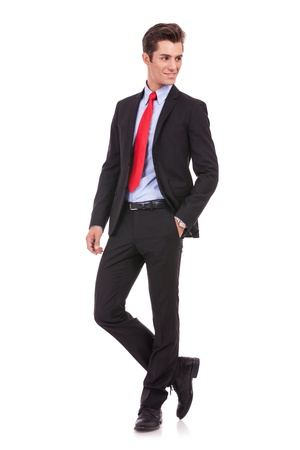 young business man with hands in pockets looking to his left side on white background.  Stock Photo - 15719673