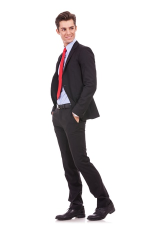 see side: side vie of a young business man standing with his hands in pockets and looking to his back on white background Stock Photo