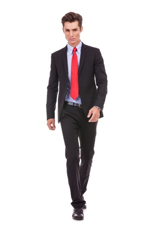 very serious young man walking forward to the camera onwhite background