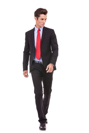 looking to the side: young businessman is walking. He is smiling and looking away from the camera to his left side. isolated over white background