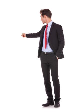 apontador: Jovem homem de neg�cios apontando para algo em suas costas no fundo branco Banco de Imagens