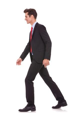 walking alone: vista lateral de un negocio a caminar hacia adelante, en el fondo blanco