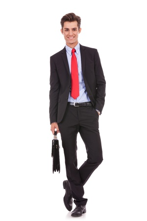 happy and relaxed business man standing with his hand in his pocket and holding a briefcase, looking at the camera Stock Photo - 15738088