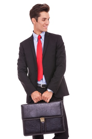 certitude: young business man holding a briefcase and looking to his left side on white background