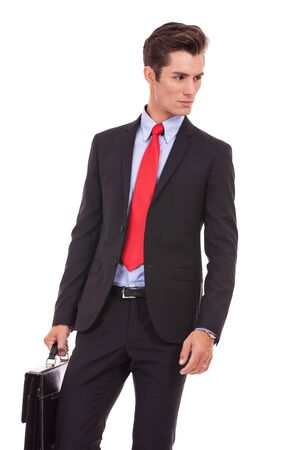 confident serious business man looking to his side while holding a suitcase Stock Photo - 15738289