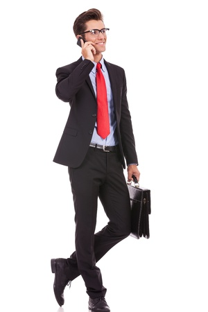 fashionable business man wearing glasses holding a briefcase and talking on his smartphone, looking away from the camera and smile photo