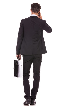 back view of a business man holding a briefcase and talking on his smartphone on white background photo