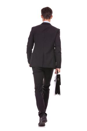 achteraanzicht van een zakenman met een aktentas en lopen vooruit onwhite achtergrond