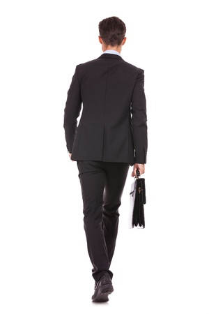 suit case: back view of a business man holding a briefcase and walking forward onwhite background