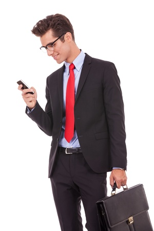 look: Handsome happy business man reading an SMS on smartphone while holding his briefcase, against white background