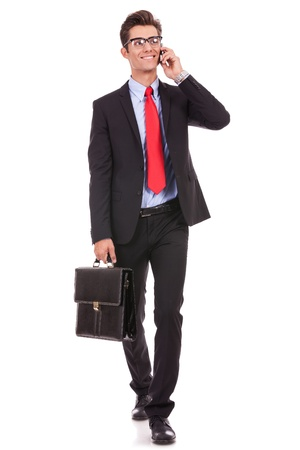 walking young business man with briefcase , looking away from the camera while speking on his smartphone, isolated on white background  photo