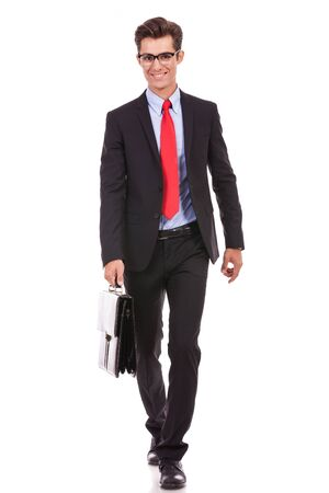 smiling business man wearing glasses is walking with a briefcase Stock Photo - 15738144
