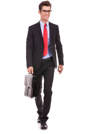 brief case: young business man is walking an looking away from the camera while holding a suitcase