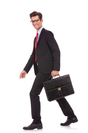 business briefcase: side view of a business man holding a briefcase and walking forward while looking at the camera Stock Photo