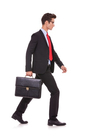 see side: side view of a serious business man holding a briefcase and walking forward on white background