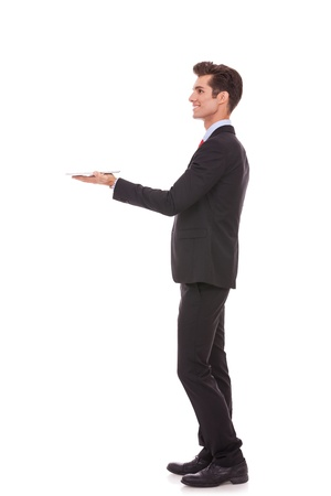 man side: side view of a young business man holding a touch screen tablet and looking up above it