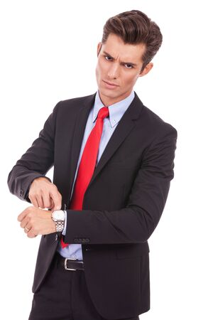 impatience: Business man impatiently pointing to his watch telling you that you are late. Isolated on white.  Stock Photo