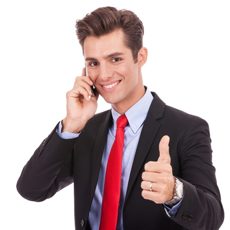 enjoy space: smiling young business man talking on the smart phone and making ok gesture. Isolated on white background