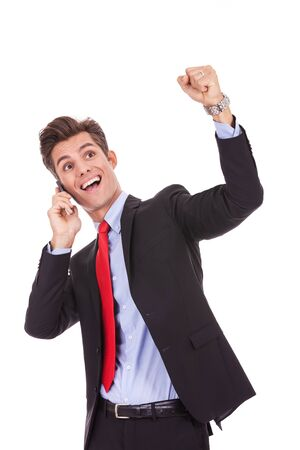 freigestellt: screaming young business man discussing on a cell phone and winning, isolated on white background