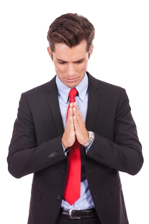 Young business man praying. Isolated against white background.  photo