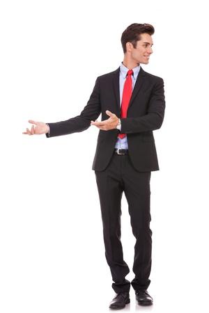 invitando: joven hombre de negocios est� dando la bienvenida y te invita a negocios en fondo blanco Foto de archivo