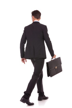 back view of a walking business man holding a briefcase and looking to his side on white background  photo