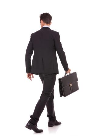 espalda: Vista posterior de un hombre de negocios caminando con un malet�n y mirando a su lado en el fondo blanco Foto de archivo