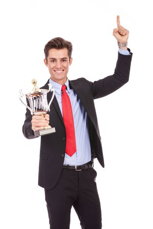 aloft: Happy business man holding a trophy aloft over white
