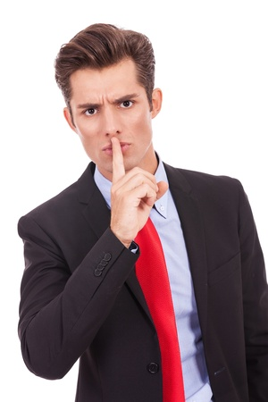 shh: business man with finger on his lips making the quiet gesture