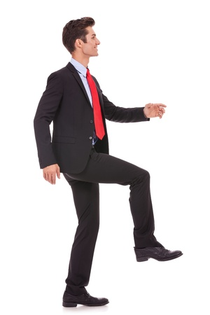 upward climb: side view of a business man stepping up and moving forward against a white background  Stock Photo