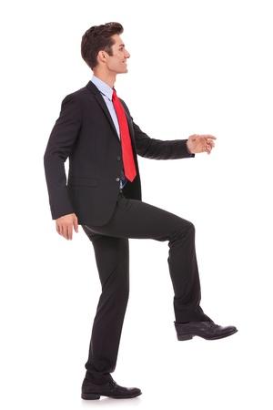 climbing stairs: vista lateral de un hombre de negocios puesto las pilas y avanzar sobre un fondo blanco