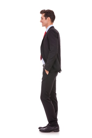 face side: Stock photo of the side view profile of a well dressed business man smiling. Full length, isolated white.