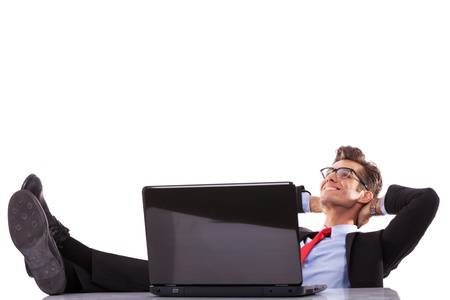 Relaxed business man working with a laptop in his office, dreaming at his success photo
