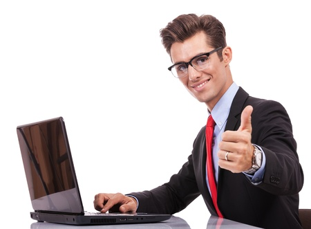 side view of a young business man working at his laptop computer and making the ok thumbs up gesture photo