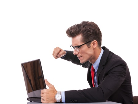 computer problem: side view of an angry business man at his laptop, on gray background