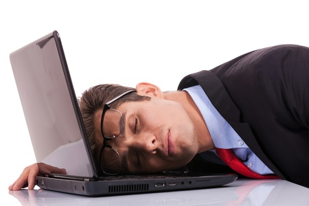Tired business man sleeping on his laptop computer Stock Photo