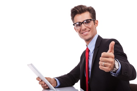 web side: side view of a young business man holding a tablet pad and making the ok thumbs up gesture at his desk Stock Photo