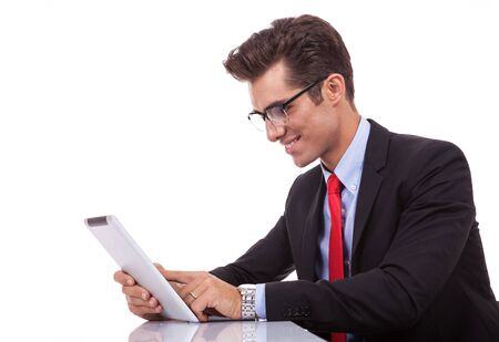 side view of a young business man browsing on his tablet pad  Stock Photo - 15738273