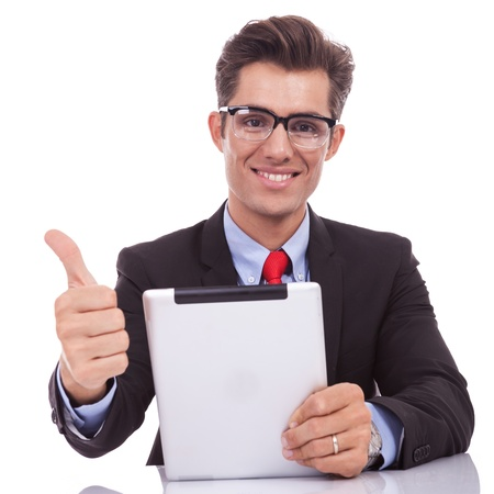 young business man making the ok thumbs up gesture while reading on his tablet pad Stock Photo - 15738151
