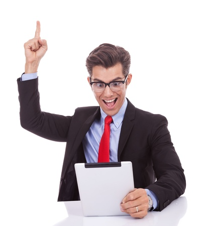 joy pad: young business man wearing glasses screaming of joy while reading the good news on the tablet pad