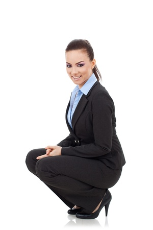 to crouch: beautiful young business woman in squat position smiling while looking at the camera with her hands between her legs