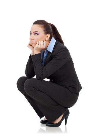 unemployed: beautiful young business woman in a squating position looking very disappointed. on white background