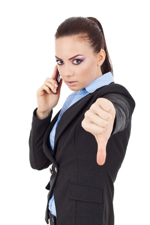 portrait of a young business woman talking on the phone and showing thumbs down photo